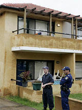 Police stand outside a western Sydney apartment block that was raided by police in the early hours of Tuesday, Nov. 8, 2005. (AP /Mark Baker)